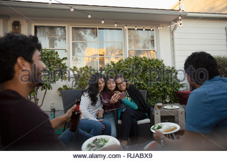 Affectionate Latinx multi-generation women taking selfie with smart phone on patio - Stock Photo