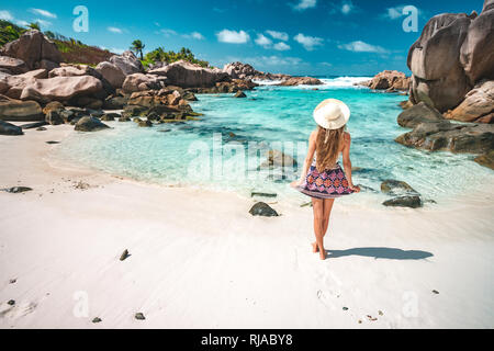 A young girl standing in shallow water on La Digue island, Seychelles - Stock Photo