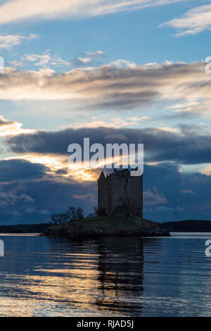 Stalker Castle with reflection on Loch Laich an inlet off Loch Linnhe at dusk, Highlands, Scotland with snow covered mountains, winter - Stock Photo