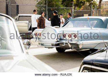 Latinx men friends hanging out in parking lot with low rider vintage cars - Stock Photo