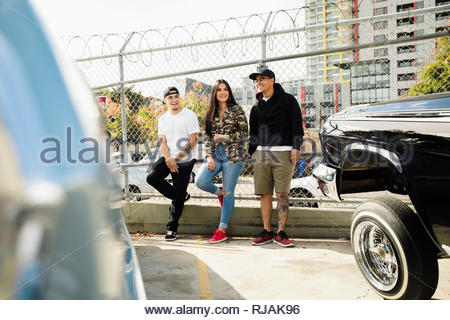 Latinx friends hanging out near low rider cars in urban parking lot - Stock Photo