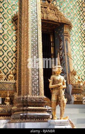 Golden yaksha statue near entrance to Phra Mondop, the library building of Wat Phra Kaew temple within Grand Palace complex in Bangkok, Thailand - Stock Photo