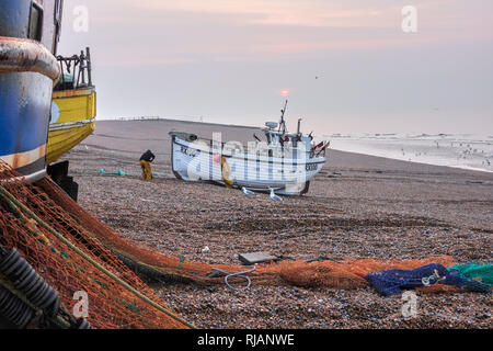 Hastings fishing boat being hauled ashore after night fishing in the English Channel. Hastings has the largest beach-launched fishing fleet in Europe. - Stock Photo