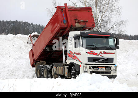 Salo, Finland - February 2, 2019: Volvo tipper truck unloads snow cleared from streets and parking lots at municipal snow dumping area. - Stock Photo