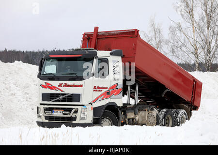 Salo, Finland - February 2, 2019: Volvo FH tipper truck unloads snow cleared from streets and parking lots at municipal snow dumping area. - Stock Photo