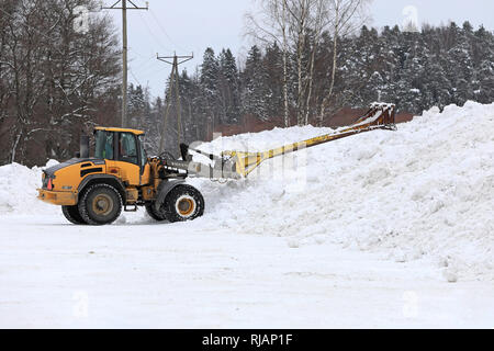 Salo, Finland - February 2, 2019: Volvo L45F wheel loader with snow handling attachment at work at municipal snow dumping area in South of Finland. - Stock Photo