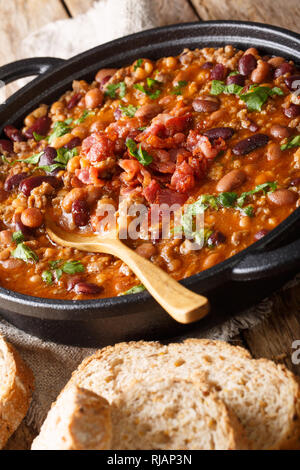 American cowboy beans with ground beef, bacon in a spicy sauce close-up on the table. vertical - Stock Photo