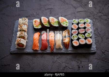Sushi rolls set with salmon and tuna fish served on black stone board - Stock Photo