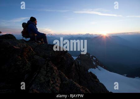Bergsteiger am Gipfelgrat des Hohen Riffler bei Sonnenaufgang, Verwall, Tirol, Österreich - Stock Photo