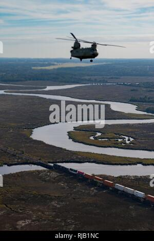 A U.S. Army Chinook maneuvers from Hunter Army Airfield to Fort Stewart during a slingload mission in support of the 3rd Division Artillery, Nov. 6, 2016. - Stock Photo
