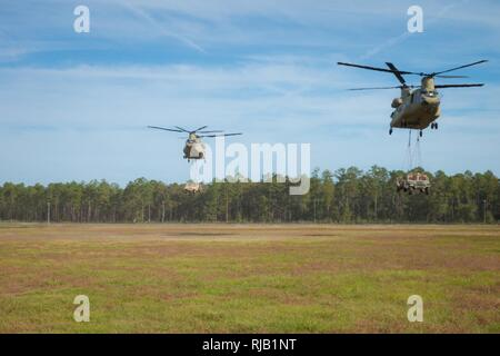 Two Chinooks assigned to 3rd Combat Aviation Briade transport Humvees and artilley pieces during a slingload training mission at Fort Stewart, Nov 6, 2016. - Stock Photo