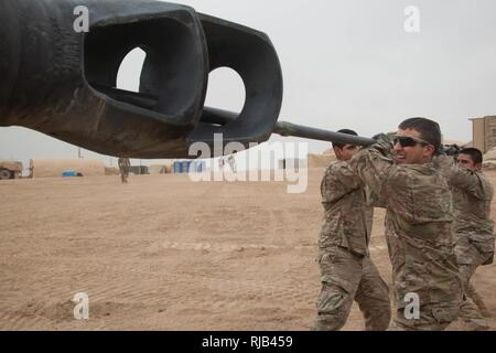 U.S Army soldiers assigned to B Battery, 4th Battalion, 1st Regiment, 1st Armor Division clean the barrel of a M109 A6 Paladin between fires missions at Camp Falcon, Iraq, Nov. 1, 2016.  B Company was conducting fires missions in support of the Coalition of regional and international nations joined together to enable Iraqi forces to counter the Islamic State of Iraq and the Levant, reestablish Iraq's borders and re-take lost terrain thereby restoring regional stability and security. Combined Joint Task Force-Operation Inherent Resolve is a multinational effort to weaken and destroy Islamic Sta - Stock Photo
