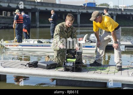BATON ROUGE, La. (Nov. 4, 2016) Petty Officer 3rd Class Darren Hauk, assigned to Explosive Ordnance Disposal Group (EODGRU) 2, explains the features of the Seabotix Remote Operated Vehicle for a member of the East Baton Rouge Sheriff's Office Dive Team during a subject matter expert exchange as part of Baton Rouge Navy Week 2016. Baton Rouge is one of select cities to host the 2016 Navy Week, a week dedicated to raising U.S. Navy awareness through local outreach, community service and exhibitions. - Stock Photo