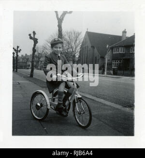 Little boy on a tricycle in a suburban street. - Stock Photo