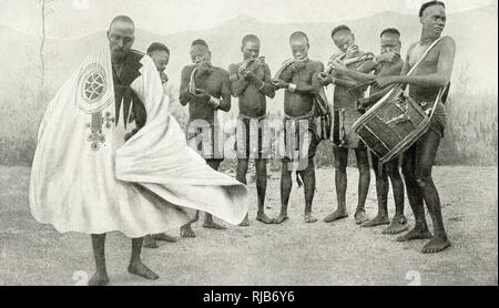 King of Yarawa dancing in a Hausa robe at Fedderi, West Africa (then part of the British Empire), with musicians alongside him. The dance was apparently performed in honour of the photographer. - Stock Photo