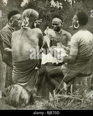 Four men playing cards in Kenya (then a British colony), East Africa. - Stock Photo