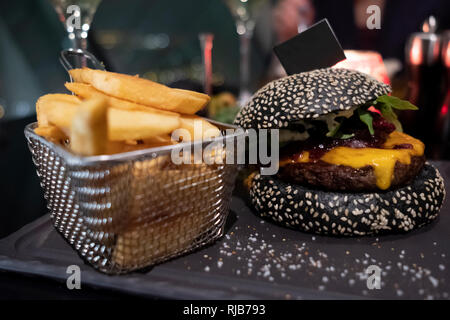 Tasty black burger and french fries in basket served on black cutting board. Copy-space flag stuck into bun for your individual text - Stock Photo