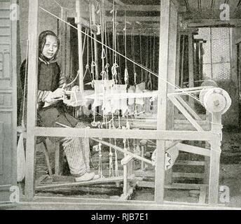 Young woman weaving cloth on a large loom, China, East Asia. - Stock Photo