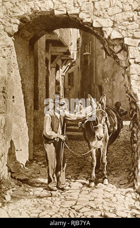 Man and donkey in a street in Puget-Theniers, Alpes-Maritimes, France. - Stock Photo