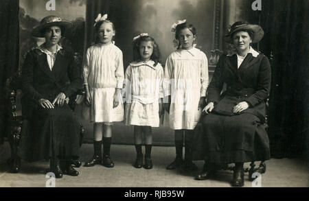 Three Young girls (sisters) posing for a formal studio photography between their seated Mother and (possibly) their Aunt. - Stock Photo
