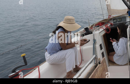 mother  with hat sitting on cockpit coaming  and daughter with cell phone sitting in the companionway of sailboat - Stock Photo