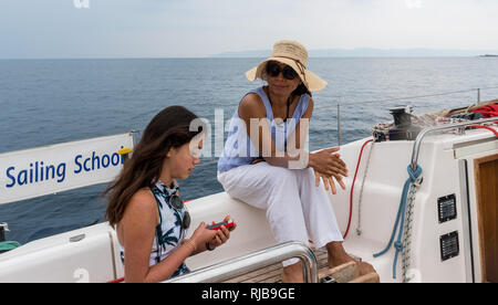 mother  with hat and daughter with cell phone sitting in the cockpit of sailboat - Stock Photo