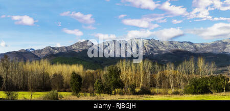 Panoramic landscape of mountains with trees and blue sky. Panoramic view of the Sierra de Gredos, Spain - Stock Photo