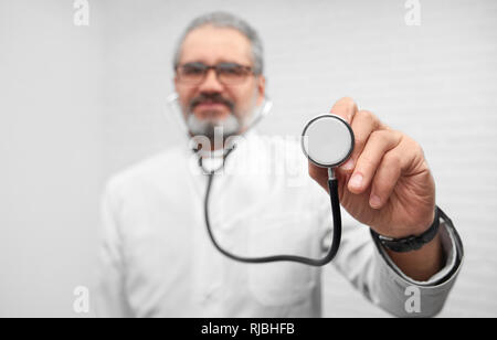 ENT doctor holding stethoscope in hand, showing it. Close up of medical equipment. Professional mature therapist wearing in white uniform and glasses looking at camera and posing. - Stock Photo