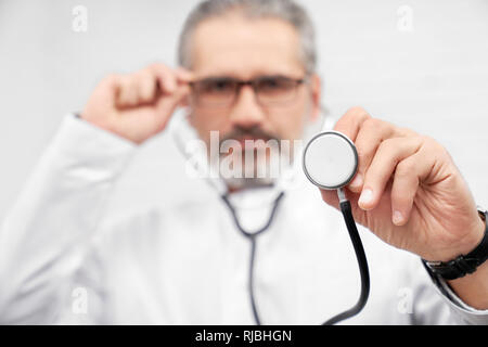 Close up of medical stethoscope. ENT doctor holding medical equipment, holding one hand on glasses. Physician looking at camera, posing in studio. - Stock Photo