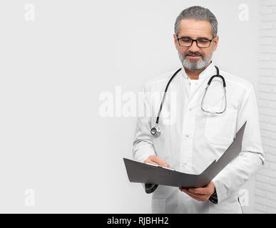 Confident ENT doctor holding folder, looking down and reading. Professional therapist with stethoscope on neck wearing in medical white coat and glasses. Studio with white background. - Stock Photo