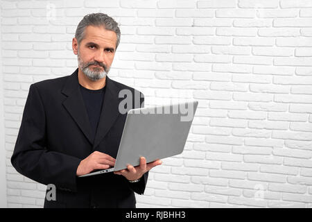 Serious and confident businessman posing in studio with white background. Handsome mature man looking at camera, holding notebook. Bearded man wearing in black outfit. - Stock Photo