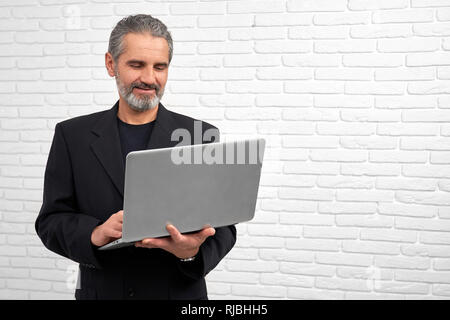 Cheerful man holding notebbok, looking down, reading and browsing. Handsome bearded man wearing in black suit. Mature businessman smiling, posing in studio with white background. - Stock Photo