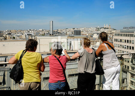 Four Female Tourists enjoy the Panoramic View over the Paris Rooftops from the Roof Terrace of the Galeries Lafayette Paris France - Stock Photo