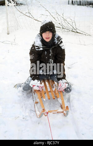 Nine year old boy tobogganing in the snow, Medstead, Alton, Hampshire, England ,United Kingdom. - Stock Photo