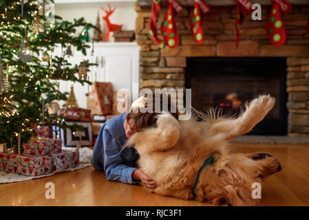 Boy lying on the floor in front of a Christmas tree cuddling his dog - Stock Photo