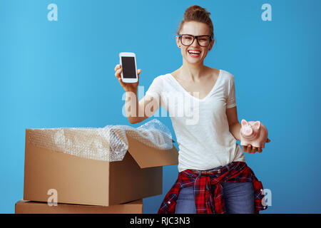 smiling young woman in white t-shirt with piggybank showing phone blank screen near cardboard box isolated on blue. Call professional movers and obtai - Stock Photo