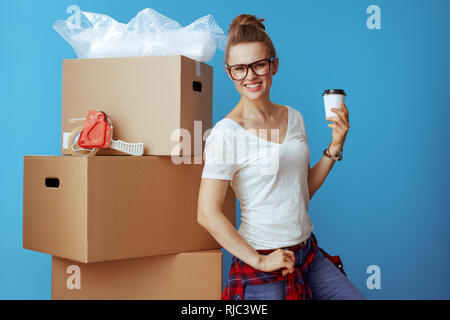 smiling modern woman in white t-shirt near cardboard box with coffee cup isolated on blue. professional movers keep you relocation stress free. - Stock Photo