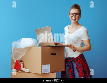 Portrait of happy modern woman in white t-shirt near cardboard box with laptop against blue background - Stock Photo