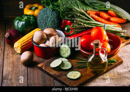 Vegetables and utensils on kitchen table - Stock Photo