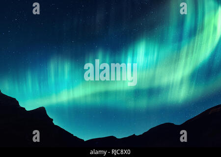 Aurora borealis. Northern lights in winter mountains. Sky with polar lights and stars - Stock Photo