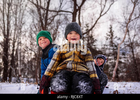 Portrait of three children sitting on a sledge, Wisconsin, United States - Stock Photo