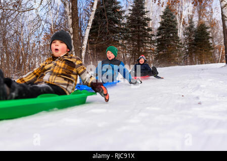 Three boys on a sledge laughing, Wisconsin, United States - Stock Photo