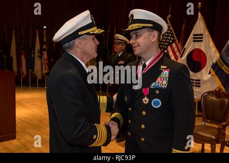 Busan, Republic of Korea (Jan 11, 2018) - Vice Adm. Phil J. Sawyer, commander, U.S. Seventh Fleet presents the Legion of Merit to Rear Adm. Brad Cooper, commander, U.S. Naval Forces Korea (CNFK) during a change of command ceremony at CNFK headquarters. During the ceremony Rear Adm. Michael E. Boyle relieved Rear Adm. Brad Cooper, becoming CNFK's 36th commander. - Stock Photo