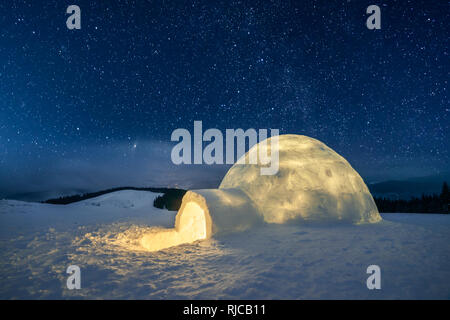 Fantastic winter landscape glowing by star light. Wintry scene with snowy igloo and milky way in night sky - Stock Photo