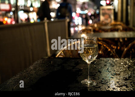 wine glass on rain drenched roadside table at night in the city - Stock Photo