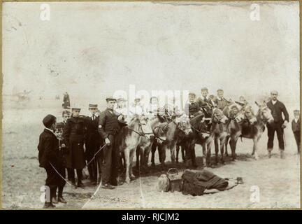 Holidaymakers with donkeys at the seaside. - Stock Photo