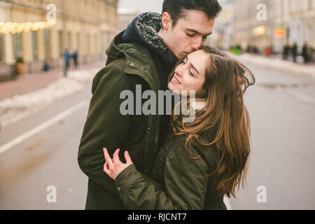 Theme love and romance. Caucasian young people heterosexual couple in love students boyfriend girl hugging and kissing on center of road in center of