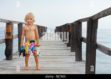 Happy little child with snorkeling mask, fins going to dive in sea to exporing underwater nature. Travel lifestyle, water sports, swimming adventure - Stock Photo