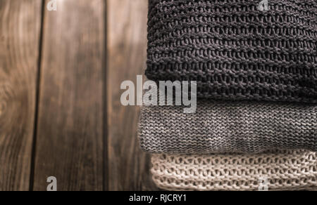 a stack of knitted sweaters in white, gray and black on a wooden background, close-up, space for text - Stock Photo