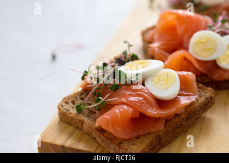 Toasts with smoked salmon and quail egg and radish sprouts  served on rustic wooden board with glasses of white wine. Delicious appetizer, snack or pa - Stock Photo